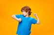 Happy red-haired boy in a blue T-shirt on a yellow background dances