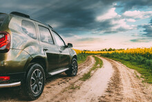 Car Renault Duster Or Dacia Duster Suv In Summer Rapeseed Field Countryside Landscape On Background Dramatic Sky