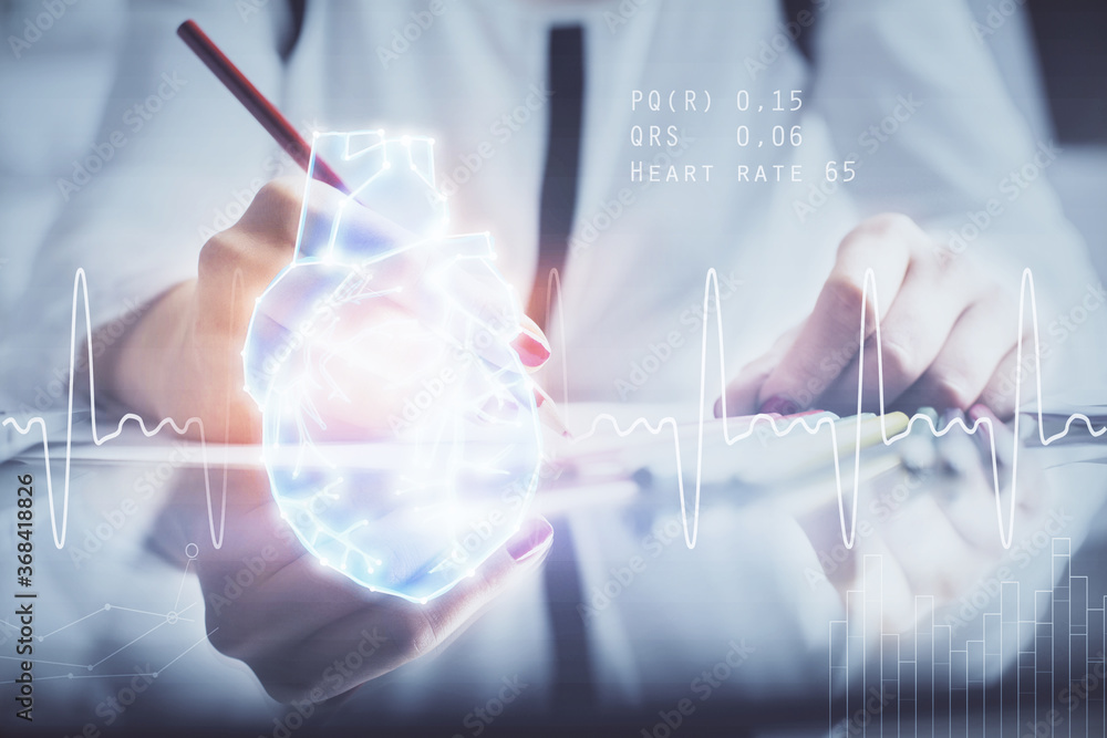 Fototapeta Heart hologram over woman's hands writing background. Concept of Medical education study. Double exposure
