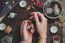Witches Hands On A Table Ready For Spell Work. Wiccan Witch Altar Filled With Sage Smudge Sticks, Herbs, White Candles. Female Witch Wearing Vintage Jewelry, Holding Citrine Crystal Rock In Her Hands