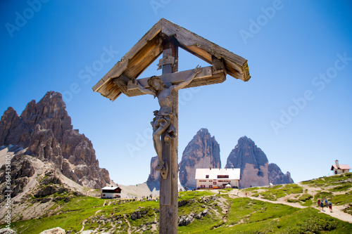 Obraz na plátně A 100 years old Crucifix, made of wood, tipical of Dolomity Region with Tre cime