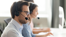 Confident Call Center Operator Agent In Headset With Microphone Consulting Client Online Close Up, Busy Employee Working In Customer Support Service Office, Coworking Space, Horizontal Photo