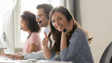 Smiling Woman Call Center Operator In Headset Showing Thumbs Up Gesture, Sitting At Workplace In Customer Support Service Office, Woman In Headphones Looking At Camera, Horizontal Photo