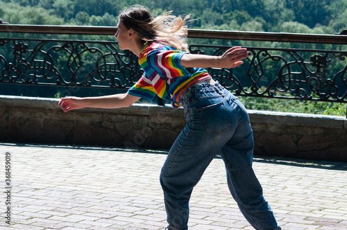 Obraz na plátne Attractive teenage girl quickly rides around the city on roller skates on a sunn