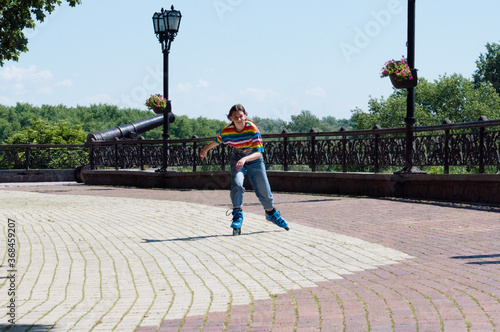 Fototapeta Attractive teenage girl quickly rides around the city on roller skates on a sunn