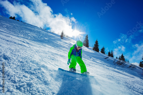 Active boy move fast on snowboard throwing snow around - motion image over blue Fototapet