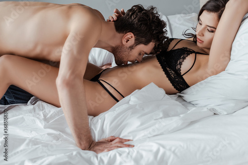 Photo Handsome man kissing belly of sexy woman in underwear on bed