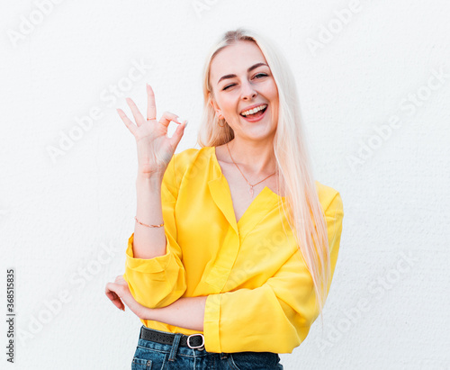Valokuva Cheerful funny cute woman with blonde hair gesturing ok