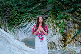 Fototapeta Zwierzęta - Young woman in white dress and plaid shirt practicing breathing yoga pranayama outdoors in moss gorge. Unity with nature concept.