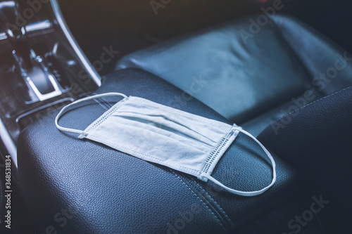 Photo Surgical mask placed on armrest box in a car