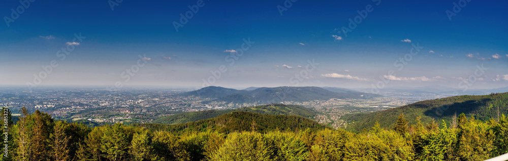 Bielsko Biala, South Poland: Wide angle from up above panoramic detailed high definition view of scenic mountains, green forest and city against blue sky