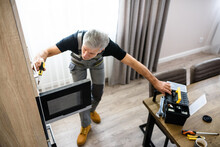 Repair Is Necessary. Full Length Shot Of Aged Repairman In Uniform Working, Fixing Broken Microwave In The Kitchen Using Screwdriver. Repair Service Concept
