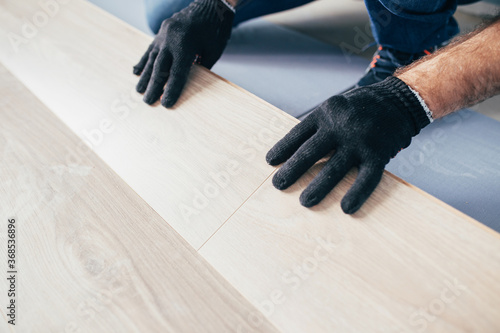 Fototapeta The master mounts the laminate on the floor - a long row assembled from panels along the entire length joins the previous one obraz na płótnie
