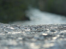 Close-up Of Rock Surface Near Stream With Bokeh Highlights In Foreground, Shallow Depth Of Field