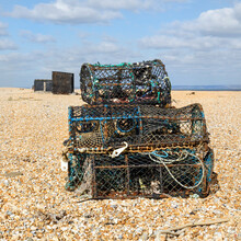 Crab Pots Stacked On Dungeness Beach Ready To Be Used To Catch Crabs When The Tide Is Right - UK.