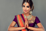 Portrait of a beautiful indian girl in a greetting pose to Namaste .India woman in traditional sari dress and jewelry.