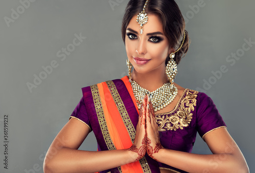 Obraz Portrait of a beautiful indian girl in a greetting pose to Namaste .India woman in traditional sari dress and jewelry. - fototapety do salonu