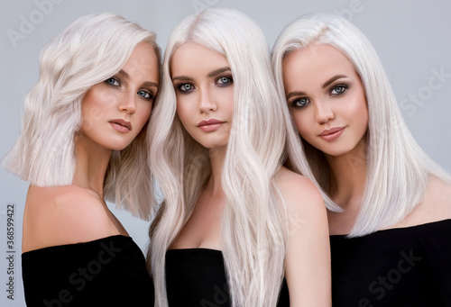 Three beautiful girls with hair coloring in ultra blond. Stylish hairstyle curls done in a beauty salon. Beauty, cosmetics and makeup