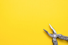 Steel Multi Tool On The Yellow Flat Lay Background.