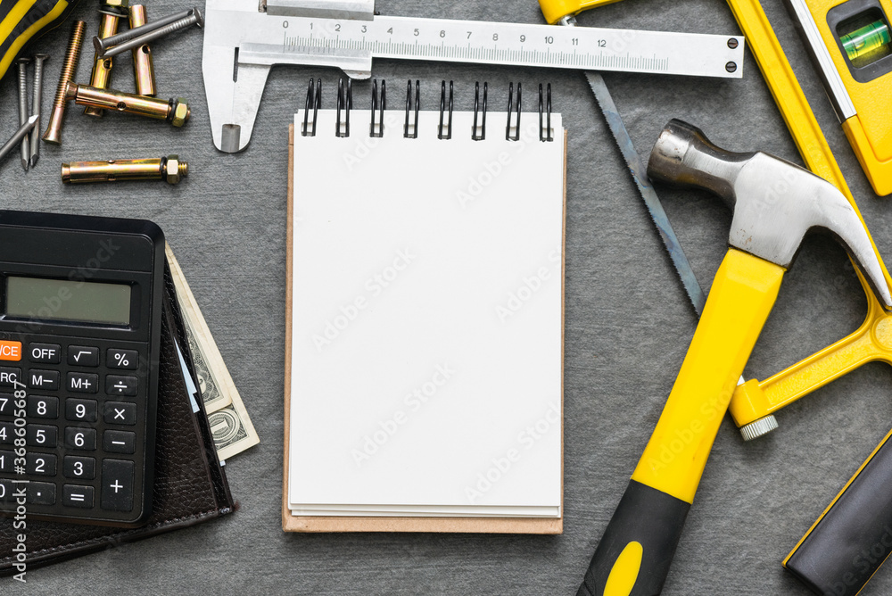 Fototapeta Construction cost or repair calculation mockup. Blank page notepad and work tools on the workbench.