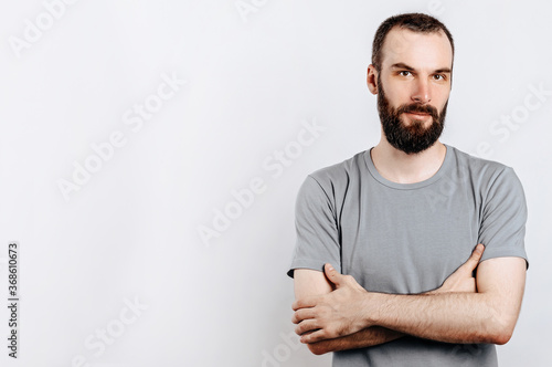 Fotografiet Portrait of a handsome brutal brunette serious man on a white background with crossed arms