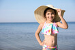 Cute little child with straw hat on sunny day. Beach holiday
