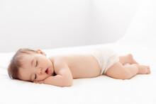 Full Body Shot Of Sleeping Baby On White Bed