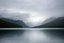 Fog And Clouds Shroud The Mountains Around Bowman Lake In Glacier National Park.