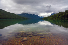 Clouds And Colorful Stones At Bowman Lake In Glacier National Park.