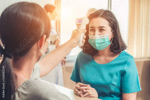 Foto Receptionist and guest wearing face mask at front desk while having conversation in office or hospital