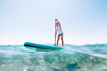 Under The Water View Angle To The Smiling Blonde Teenager Boy Rowing Stand Up Paddle Board. Active Family Summer Vacation Time Near The Sea Concept Image.