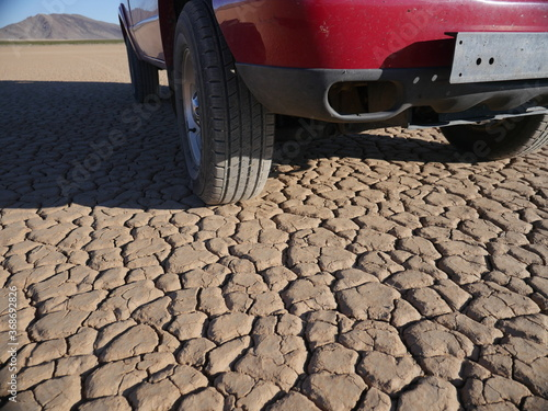 A truck parked on a dry lake bed in the desert Canvas Print