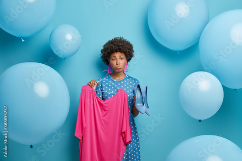 Upset woman has problem of what to wear, holds pink dress on hanger and blue high heel shoes, sad clothing items doesnt match, chooses outfit for special occasion, expresses negative emotions
