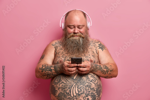 Pleased plump man with naked tattoed body, big belly, listens music in headphones, holds cellular, downloads songs in playlist, isolated on pink background Wallpaper Mural