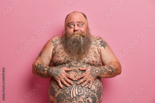 Obraz Bearded thick guy keeps hands on big tattoed belly, has bugged eyes, has thick beard, poses against pink background. Naked overweight adult man with large tummy, asks advice how to loose weight - fototapety do salonu