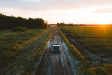 Aerial View Of Suv Vehicle Driving On Countryside Road During Sunset In Summer.