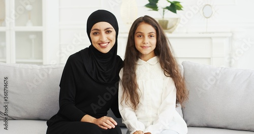 Obraz na plátně Portrait of beautiful young Arabic woman in black hijab looking at her pretty cute teen daughter with love