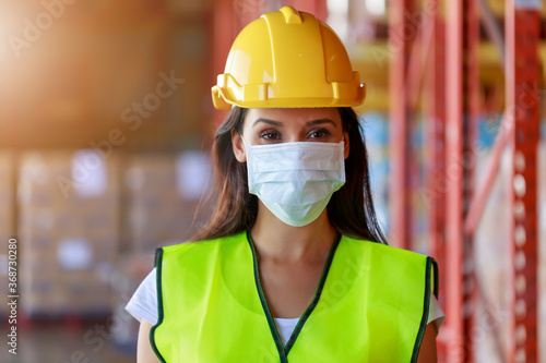 Foto Young Attractive Hispanic Latin ethnic women wearing protective face mask during working in warehouse, new normal after Covid-19 pandemic crisis