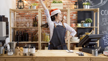 Woman Coffeehouse Staff Against Red Bricks Wall Listening To Music And Dancing In Counter Bar. Girl Barista In Santa Hat Having Fun And Moving In Cafe Store. Waitress Enjoy Christmas Party In Shop
