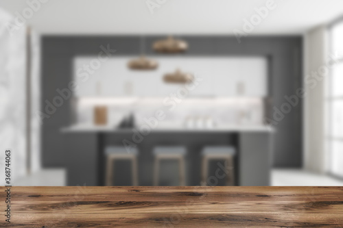 Fototapeta Table in blurry white and grey kitchen