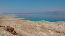 Dead Sea Landscape Wide Angle Shot. Dessert Terrain With Sinkholes In The Foreground And Mountains Of Jordan In Far Background.