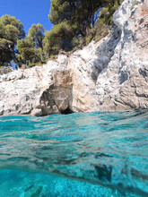 Underwater Split Line Photo Of Beautiful Caves With Deep Turquoise Sea And Pine Trees Of Kastani Beach Well Known For Mamma Mia Movie Filming, Skopelos Island, Sporades, Greece