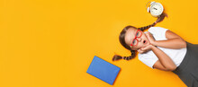 Shocked Schoolgirl With An Alarm Clock And A Book On A Yellow Background. Back To School Concept Top View Banner Copy Space