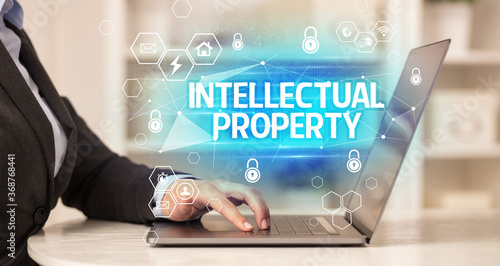 Fototapety, obrazy: INTELLECTUAL PROPERTY inscription on laptop, internet security and data protection concept, blockchain and cybersecurity