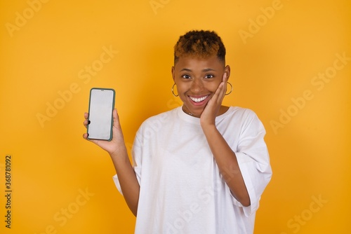 Fototapeta Young African American girl with afro short hair wearing white tshirt standing h