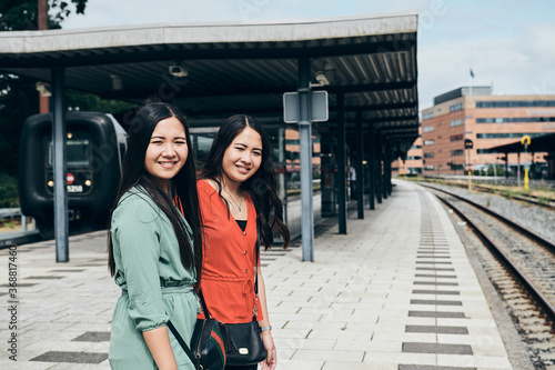 Photo Side view of young Asian girls in casual clothes smiling and looking at camera w