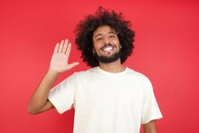 Young Handsome Man Standing Over Yellow Isolated Background Waiving Saying Hello Or Goodbye Happy And Smiling, Friendly Welcome Gesture