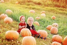 Two Little Girls With Orange Pumpkins At Sunset
