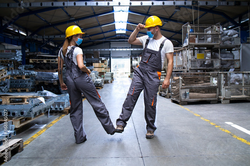 Foto Workers wearing uniforms and hardhat at factory touching with legs and greeting due to corona virus and infection