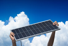 Hand Holding A Solar Panel On Blue Sky Background,alternative Clean Green Energy Concept